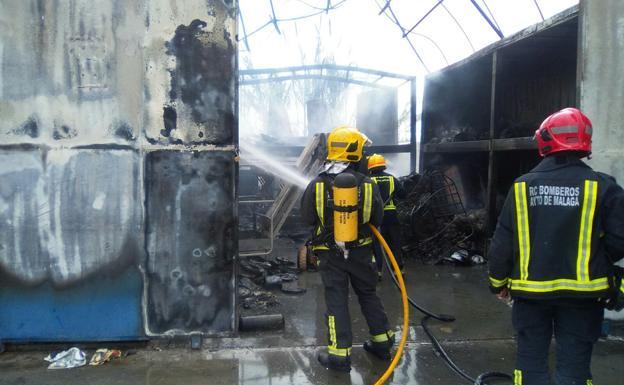 Los bomberos, en el contenedor afectado por las llamas./