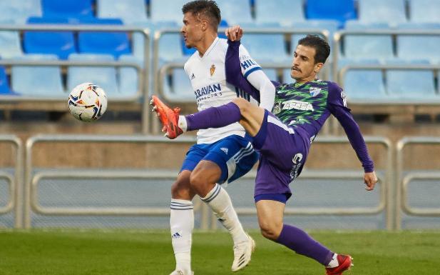 El lateral izquierdo malaguista Matos trata de anticiparse a Narváez. /AGENCIA LOF